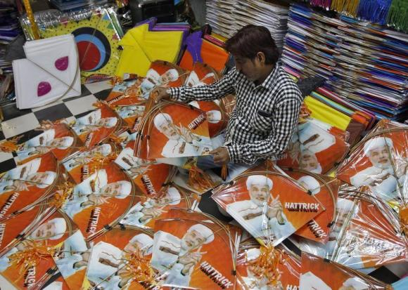 A kite maker counts kites with images of Hindu nationalist Narendra Modi, prime ministerial candidate for India's main opposition BJP and Gujarat's chief minister, at a workshop in Ahmedabad