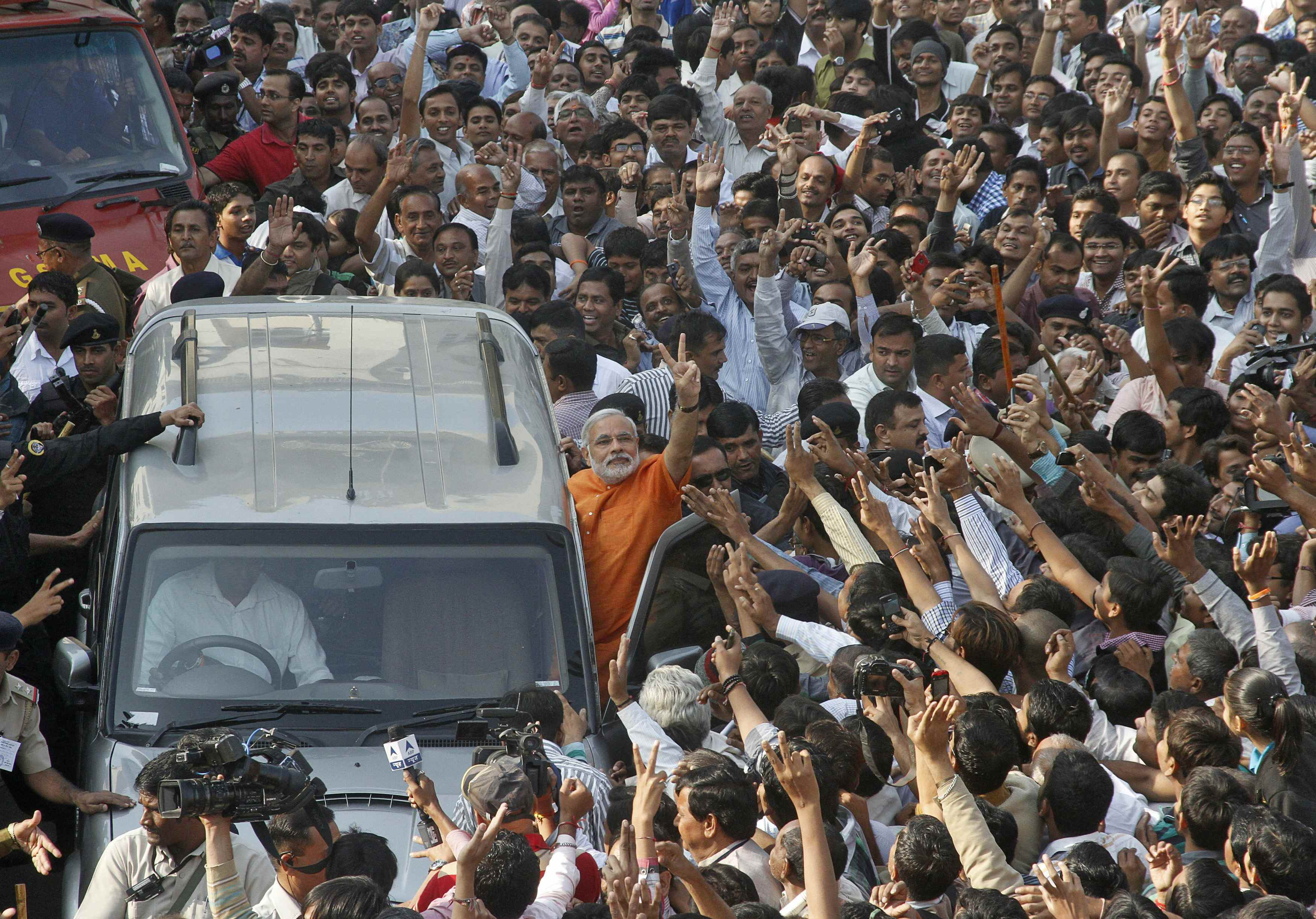 Gujarat state Chief Minister Narendra Modi gestures from his car after casting his vote during the second phase of state elections in the western Indian city of Ahmedabad